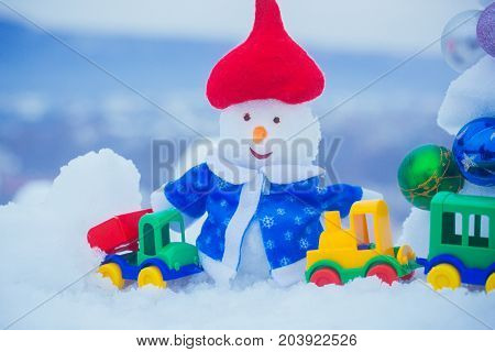 Snowman In Red Hat And Blue Coat On Snowy Background