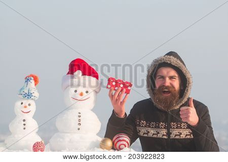 Happy Man Showing Thumbs Up Hand Gesture With Present Box