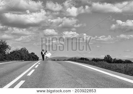 Beautiful bride and handsome groom elegant fashion married couple in wedding dress and suit run along road and hold hands on blue sky