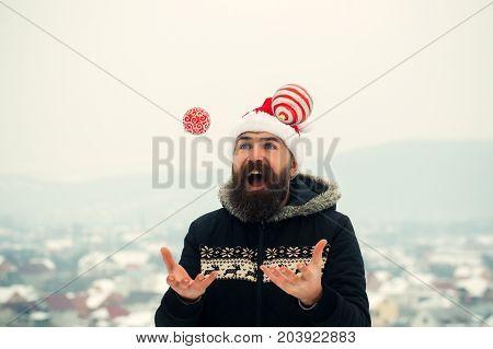 Santa Man Juggling Xmas Balls On Snowy Landscape