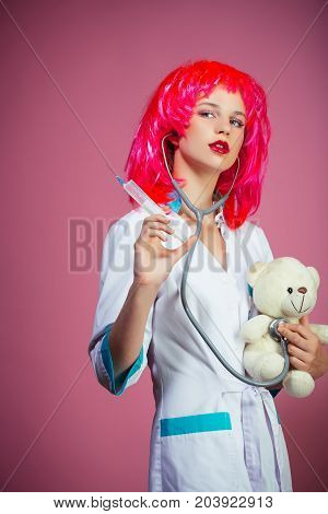 Nurse in red wig on pink background. Woman wearing medical uniform with stethoscope. Doctor and patient. Health care and cure concept. Girl curing teddy bear toy with syringe.