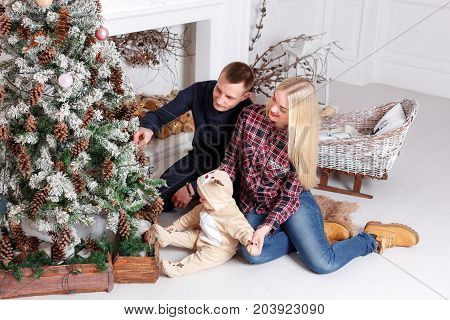Happy family at Christmas. The parents and the baby lying on the floor and smiling. In the background stands and Christmas tree ornaments.