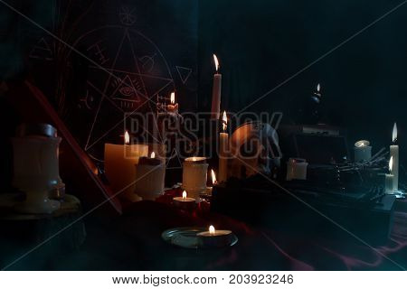 Witchcraft composition with burning candles, books, jewelry and pentagram symbol. Halloween and occult concept, black magic ritual.