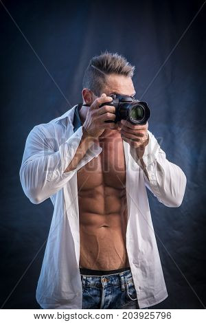 Adult muscular man in shirt standing and taking shots with camera in studio.