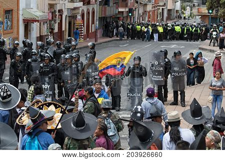 June 24 2017 Cotacachi Ecuador: riot police behind shields separating dancer groups during the Inti Raymi parade to avoid violence