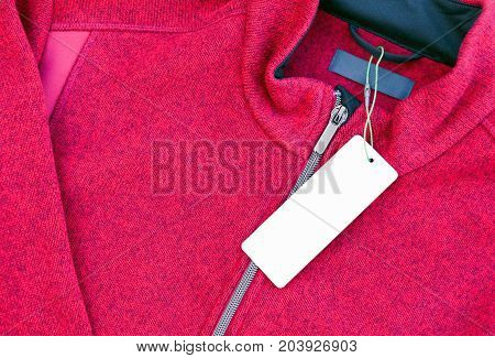 White blank clothing label tag on a new red jacket with zipper