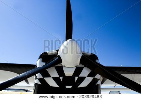 Black Propellor on a Black and White Airplane Agaist a Bright Blue Sky
