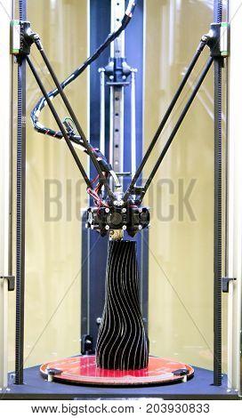 3d printer prints a model of a black vase close-up. Progressive modern additive technologies 4.0 industrial revolution