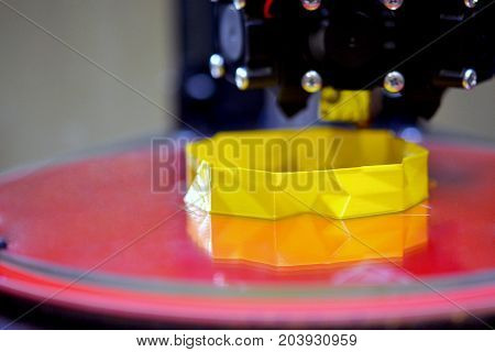 3d printer while printing a yellow object close-up close-up. Progressive modern additive technologies 4.0 industrial revolution