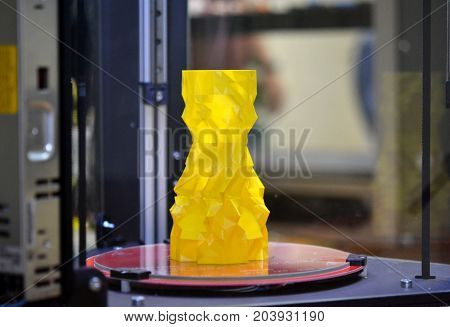 The object in the form of a yellow vase stands on the desktop of a three-axis 3d printer close-up. Progressive modern additive technologies 4.0 industrial revolution