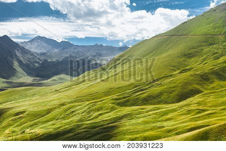 Picturesque Mountain Landscape. Green Hill And Mountain Range On A Sunny Summer Day. Elbrus Region North Caucasus Russia