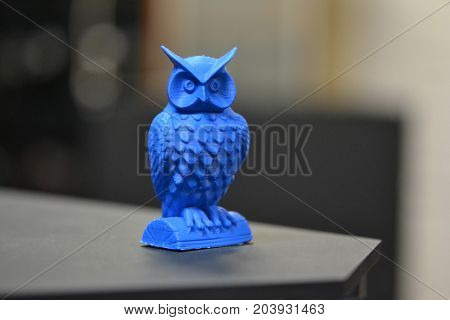 An owl made on a 3d printer stands on a blurry dark background close-up. Progressive modern additive technologies 4.0 industrial revolution