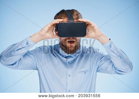 man in virtual reality glasses on a blue background.