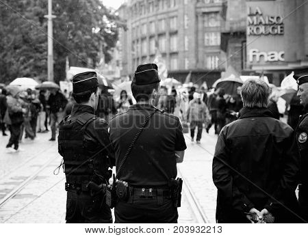 STRASBOURG FRANCE - SEPT 12 2017: Police under rain surveillance of people at political march during a French Nationwide day of protest against the labor reform proposed by Emmanuel Macron Government