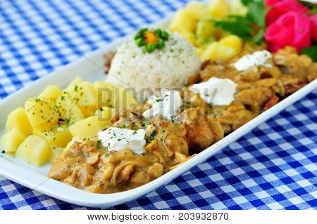 Meal of mushrooms in sauce with rice and potatoes