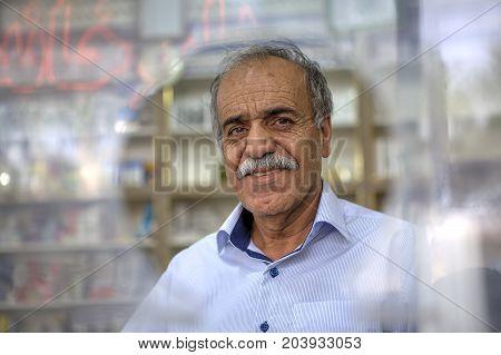 Fars Province Shiraz Iran - 18 april 2017: Elderly man standing in front of round window on city street.
