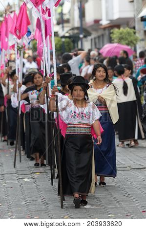 April 14 2017 CotacachiEcuador: indigenous kechwa women in traditional dress walking with religious flags at the Easter procession