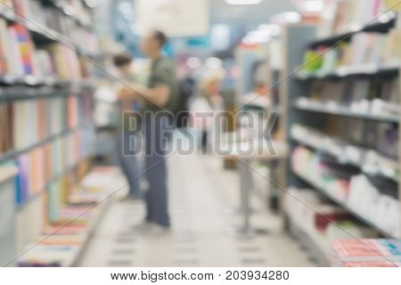 Blurred bookshelves in book store or in library. Unrecognizable silhouettes of people, chooses necessary book. Education concept, reading fiction, life style