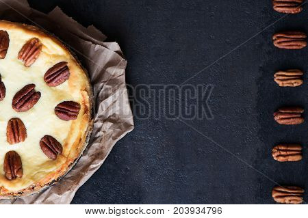 Cheesecake with pecan nuts on a black background. With copy space