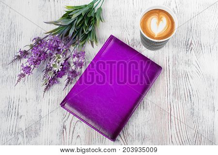 A purple notepad cup of coffee flowers on a white wooden background