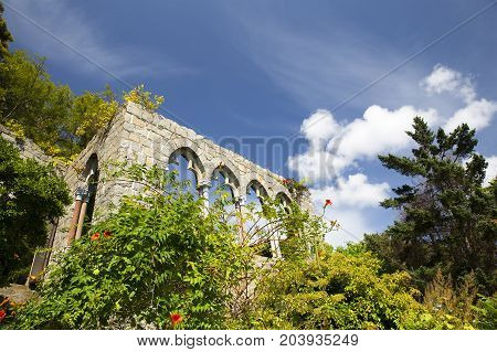 ruins of an ancient castle among flowers and trees. arched gallery on a background of blue sky. Copy space for your text