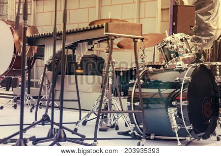 A drum set a musical instrument stands on the stage in the street. toning