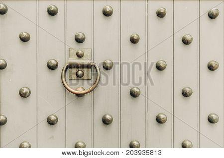 wooden door with metal spikes. Metal rivet and knocker on old doors