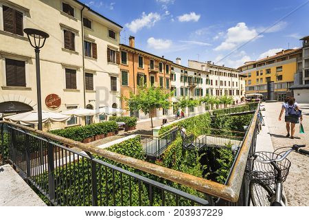 VERONA ITALY - JUNE 25 2016: Picture from Piazza Cittadella with restaurants trees people and a wide green garden with stairs in a sunny day with clouds. Verona Italy.