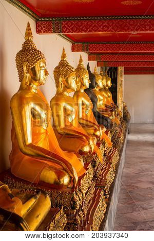 Row of sitting Buddha statues facing right inside Wat Pho or Temple of the reclining Buddha Bangkok Thailand