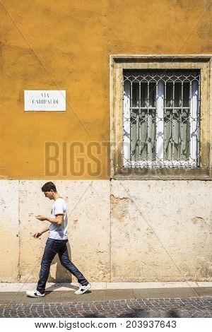 VERONA ITALY - JUNE 25 2016: Young man passing by a colorful texturized wall with a window with bars in Via Garibaldi in a sunny day. Verona Italy.