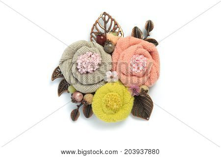 Brooch handmade from a fabric consisting of three flowers of gray pink and yellow colors