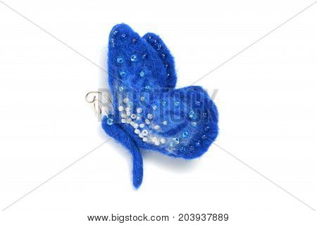 Handmade brooch from felt in the form of a blue butterfly decorated with beads on a white background