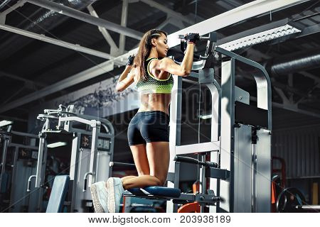 Woman doing pull ups on simulator in gym