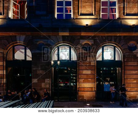 STRASBOURG FRANCE - SEPT 18 2014: Night view of Apple Store facade builing with impatient customers waiting in queue and tents for the upcoming Apple iPhone Apple Watch and other new products
