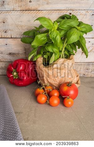Fresh basil and other ingredients for Italian cuisine. Cherry tomatoes basil and red pepper on wooden table for use as cooking ingredients