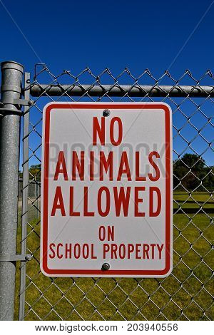 Metal sign on fence owned by a school district prohibiting animals on property