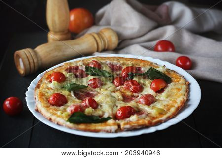 Hot pizza slice with melting cheese on a dark wooden table with tomatos.Gray drape.