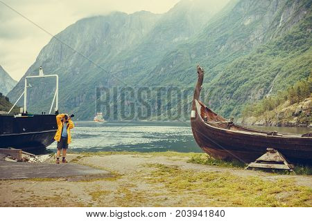Male tourist with camera taking photo of old wooden viking boat on seashore in norwegian nature foggy misty day. Mountains and fjord Sognefjord. Tourism and traveling concept