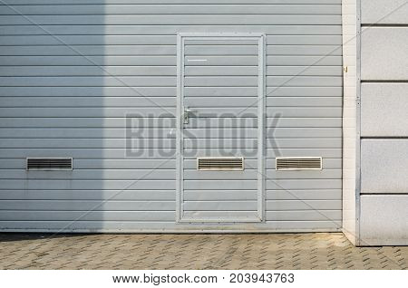Gray garage gate with ventilation grilles. Large automatic up and over garage door with inclusion of smaller personal door.