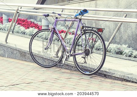 Old road bike of pink color with a ridiculous seat rewound blue electrical tape. Cycling or commuting in city urban environment ecological transportation concept poster