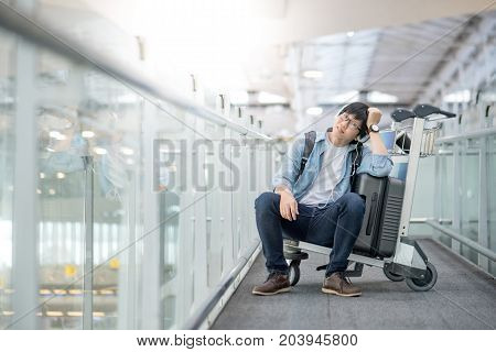 Young Asian man sitting on airport trolley with his suitcase luggage in the international airport terminal waiting for travel abroad