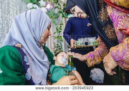 Labuan,Malaysia-July 30,2017:Aqiqah ceremony in Malay traditional ceremony at Labuan,Malaysia.The shaving of the head symbolises the cleansing of the baby from impurities & the start of its life afresh in the presence of Allah.
