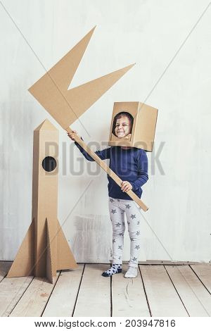 Child Little Girls Playing Spaceman With A Cardboard Rocket And A Cardboard Helmet