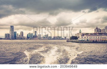New York USA - 28 September 2016: View of Pier A Harbor House in the mid-ground with New Jersey Cityscape in the background taken from a New York Water Taxi on a cloudy day.
