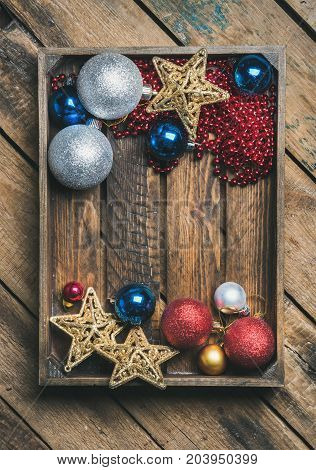 Flat-lay of Christmas or New Year holiday decoration background. Christmas tree glittering toy stars, balls and garland in wooden box over rustic wooden background, top view, copy space, verticalcomposition