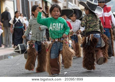 June 24 2017 Cotacachi Ecuador: indigenous quechua children wearing chaps and sombreros participating at the Inti Raymi parade