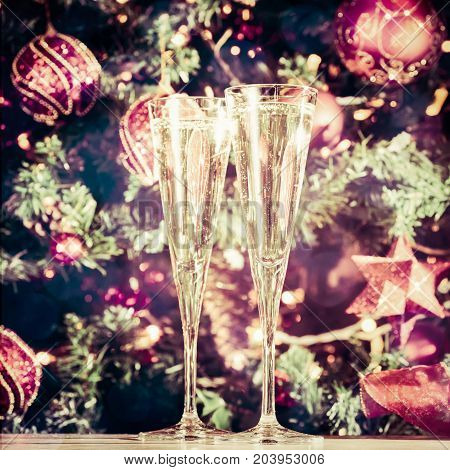 Two Glasses Of Champagne With Christmas Tree Background And Sparkles. Holiday Season Background. Tra