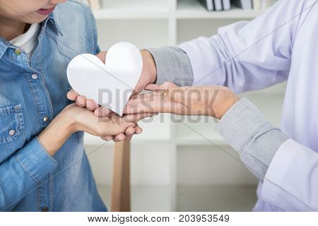 charity health care donation and medicine concept - doctor man hand giving heart to patient