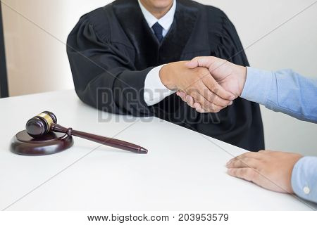 Gavel Justice hammer on wooden table with judge and client shaking hands after adviced in background at courtroom lawyer service concept