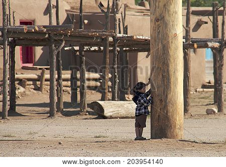 TAOS, NEW MEXICO - OCTOBER 2, 2011: A little girl playing outside of North House of the Taos Pueblo near Taos in New Mexico.